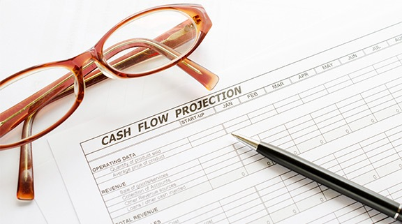 cash flow projection sheet and glasses